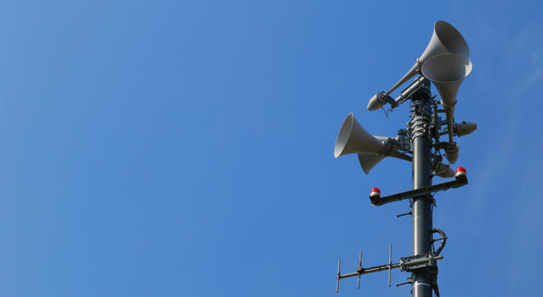 Spectacle of sunny blue sky and outdoor emergency broadcast speaker