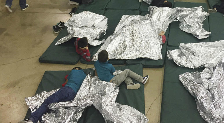 this June 17, 2018 file photo provided by U.S. Customs and Border Protection, people who've been taken into custody related to cases of illegal entry into the United States, rest in one of the cages at a facility in McAllen, Texas.