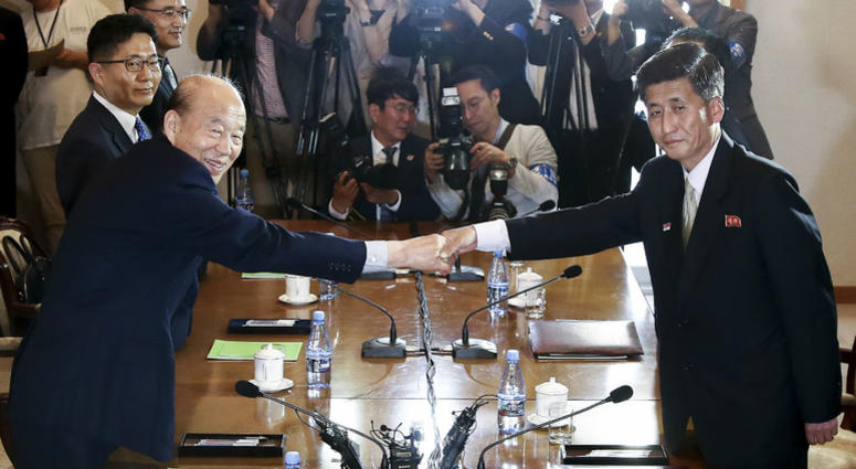 In this photo provided by South Korea Unification Ministry, South Korean Red Cross President Park Kyung-seo, second from left, shakes hands with his North Korean counterpart Pak Yong Il.