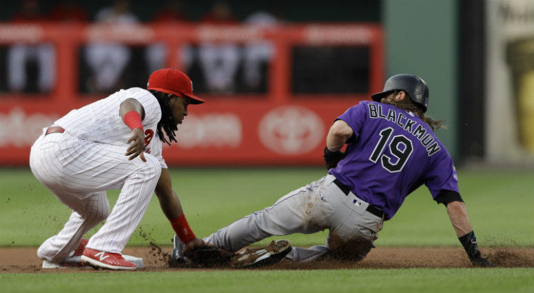 Philadelphia Phillies third baseman Maikel Franco, left, tags out Colorado Rockies' Charlie Blackmon at second base after Blackmon tried to steal during the first inning of a baseball game, Wednesday, June 13, 2018, in Philadelphia.
