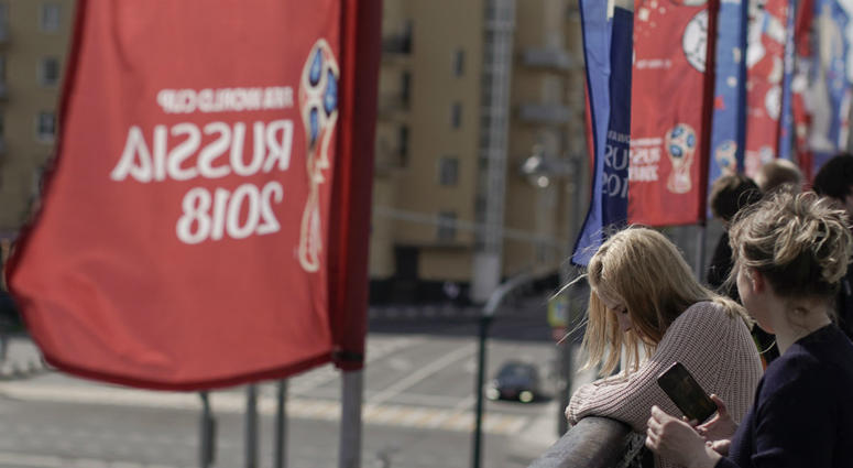 Women look over from the Krymsky Bridge, adorned with banners of the 2018 soccer World Cup, in Moscow, Russia, Wednesday, June 13, 2018.
