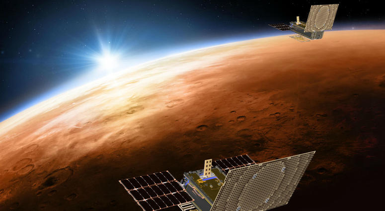 Twin Mars Cube One project (MarCO) spacecrafts flying over Mars with Earth and the sun in the distance.
