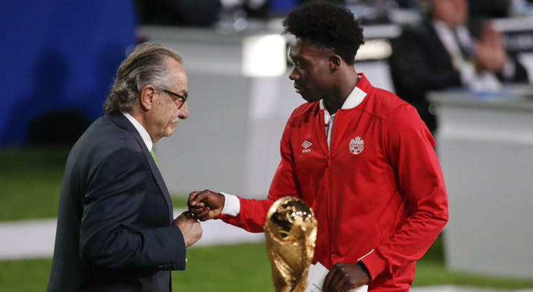 Decio de Maria, President of the Football Association of Mexico, left, and Canadian soccer player Alphonso Davies, right