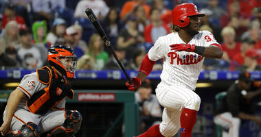 Philadelphia Phillies' Odubel Herrera, right, follows through after hitting a run-scoring single off San Francisco Giants starting pitcher Derek Holland as catcher Buster Posey, left, looks on during the third inning of a baseball game.