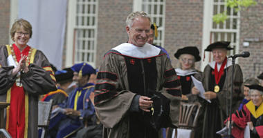 Brown University President Christina Paxson, left, and other faculty members applaud as the singer Sting, leaves the stage at Brown University Commencement.