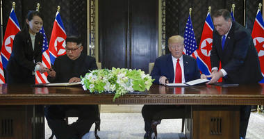North Korea leader Kim Jong Un and U.S. President Donald Trump prepare to sign a document at the Capella resort on Sentosa Island in Singapore.
