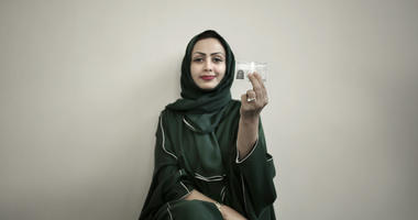 34-year old Asmaa al-Assdmi poses for a photograph holding her new car license at the Saudi Driving School inside Princess Nora University in Saudi Arabia.