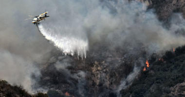 A Los Angeles County Fire Department helicopter drops water on a brush fire that erupted on a mountainside above suburban Burbank, Calif. on Saturday, July 7, 2018.