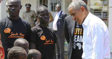 Former US President Barack Obama, right, talk to children in Kogelo, Kisumu, Kenya, Monday, July 16, 2018. Obama is in Kenya to launch a sports and training center founded by his half-sister, Auma Obama.