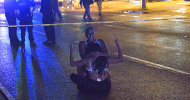 People react at the scene of a shooting in New Orleans, Saturday, July 28, 2018.