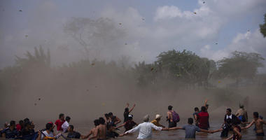 Dust clouds are created by a Mexican Federal Police helicopter flying close to the Suchiate River that connects Mexico and Guatemala, in order to create a downwash force to discourage a new group of Central American migrants bound for the U.S border, in w