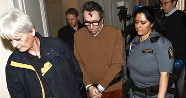 FILE - In this Monday, Nov. 12, 2018 file photo, Jean-Claude Arnault, center, is escorted from court after the first day of his appeal trial, in Stockholm.