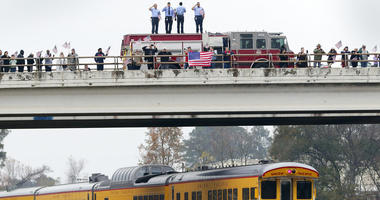 Firefighters stand on their truck and salute along with other attendants on an overpass as the train carrying the body of former president George H.W. Bush travels past on the way to Bush's final internment Thursday, Dec. 6, 2018, in Spring, Texas.