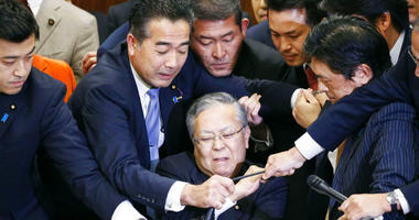 Japan's ruling parties and opposition parties' members scramble for a microphone as opposition parties try to stop Judicial Affairs Committee Chairman Shinichi Yokoyama, bottom center, from moving to hold a vote for a bill to revise an immigration control