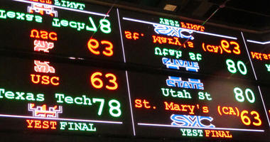 A scrolling video board with basketball scores