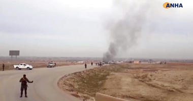 This frame grab from video provided by Hawar News, ANHA, the news agency for the semi-autonomous Kurdish areas in Syria, shows Kurdish fighters standing guard at the site of a suicide attack near the town of Shaddadeh, Jan. 21, 2019.