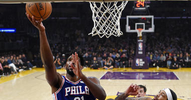Philadelphia 76ers center Joel Embiid, left, shoots as Los Angeles Lakers forward Brandon Ingram, right, defends during the first half of an NBA basketball game Tuesday, Jan. 29, 2019, in Los Angeles.