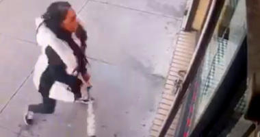 """In this Jan. 15, 2019 image taken from surveillance video, a woman smashes the windows of """"Back Home Restaurant"""" in the Bronx borough of New York."""
