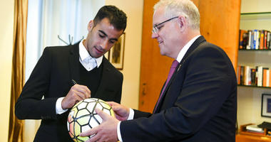 Refugee Hakeem al-Araibi, left, signs a ball for Australian Prime Minister Scott Morrison at Parliament House in Canberra, Australia, Thursday, Feb. 14, 2019.