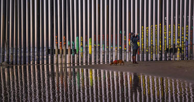 FILE - In this Jan. 3, 2019, file photo, a woman takes a snapshot by the border fence between San Diego, Calif., and Tijuana, as seen from Mexico.
