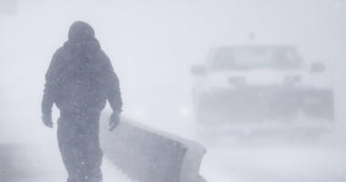 A man crosses Crow Creek during a blizzard.