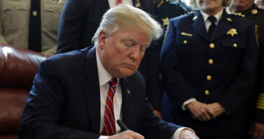 President Donald Trump signs the first veto of his presidency in the Oval Office of the White House.