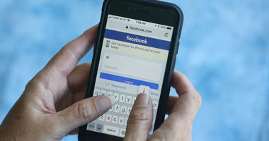 A Facebook start page is shown on a smartphone in Surfside, Fla.