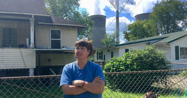 In this Aug. 23, 2018 photo, Andrea Maxey of Poca, W.Va., speaks outside her home with the American Electric Power's John Amos coal-fired power plant is in the background across the Kanawha River in Winfield.