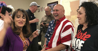 In this Tuesday, June 12, 2018 photo Nevada brothel owner Dennis Hof, second from right celebrates after winning the primary election in Pahrump, Nev