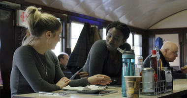 Waitress Kelcie Tipping, left, speaks with fellow waitress Mariam Touray, right, at the Modern Diner in Pawtucket, R.I.
