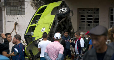 People stand around a car that was overturned by a tornado in Havana, Cuba, Monday, Jan. 28, 2019.