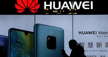 A woman browses her smartphone as she walks by a Huawei store at a shopping mall in Beijing.