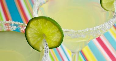 Two margaritas on a brightly colored surface