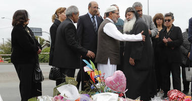 Imam Ibrahim Abdul Halim of the Linwood mosque, center left, is embraced by Father Felimoun El-Baramoussy, center right, from the Coptic Church at the site of Friday's shooting outside the Linwood mosque in Christchurch, New Zealand, Monday, March 18, 201