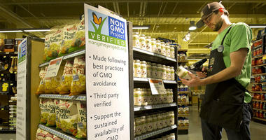 Whole Foods Market employee Ian Purdue scans non-GMO products for ordering.