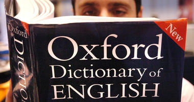 A man reading a copy of the Oxford Dictionary of English