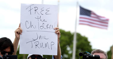 Protester Melissa Houtte holds her sign while Sen. Bill Nelson and Congresswoman Debbie Wasserman Schultz address the media after being denied access to visit the Homestead Temporary Shelter for Unaccompanied Children on June 19, 2018 in Homestead, Fla.
