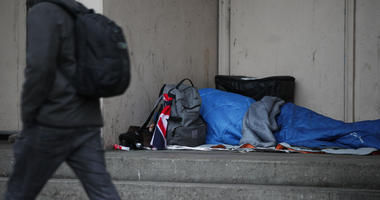 A homeless person sleeping in a doorway.