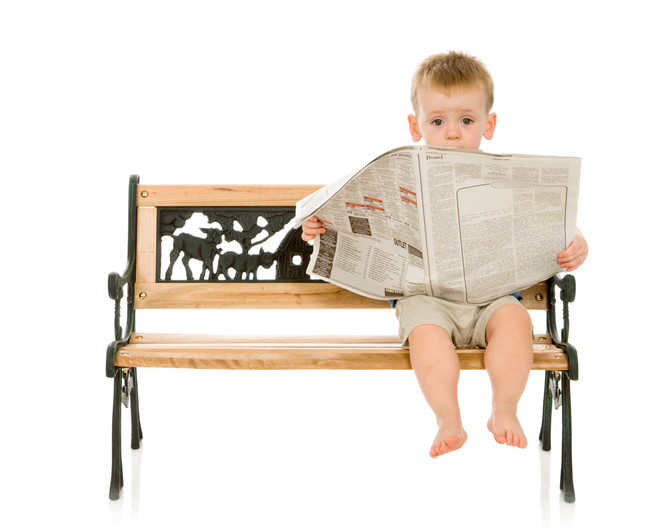 Toddler boy sitting on a bench holding a newspaper.
