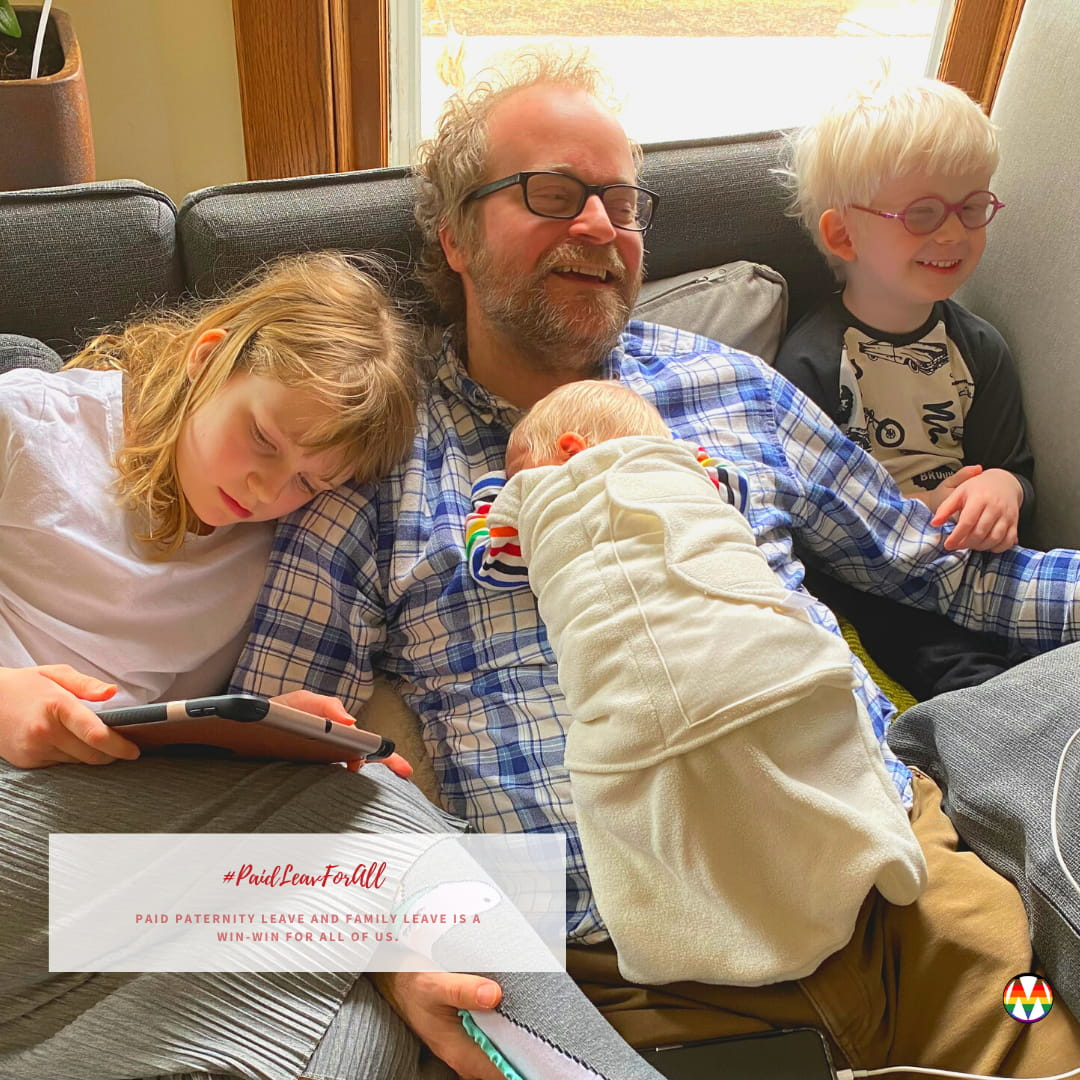 Dad with 2 kids on a couch and a baby lying on him