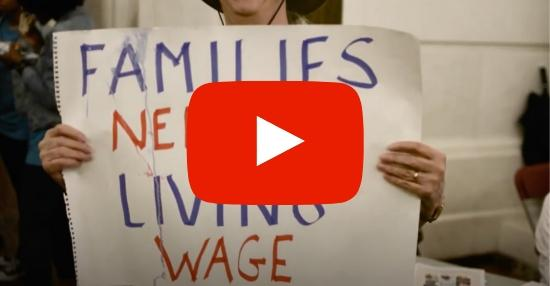 YouTube icon overlaid on image of a woman holding a sign that says Families Need a Living Wage