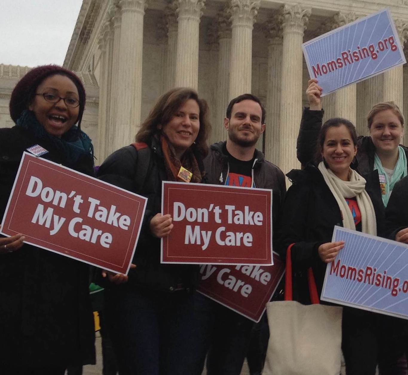 "A diverse group of people standing in front of the Supreme Court hold signs that say ""Don't Take My Care!"""