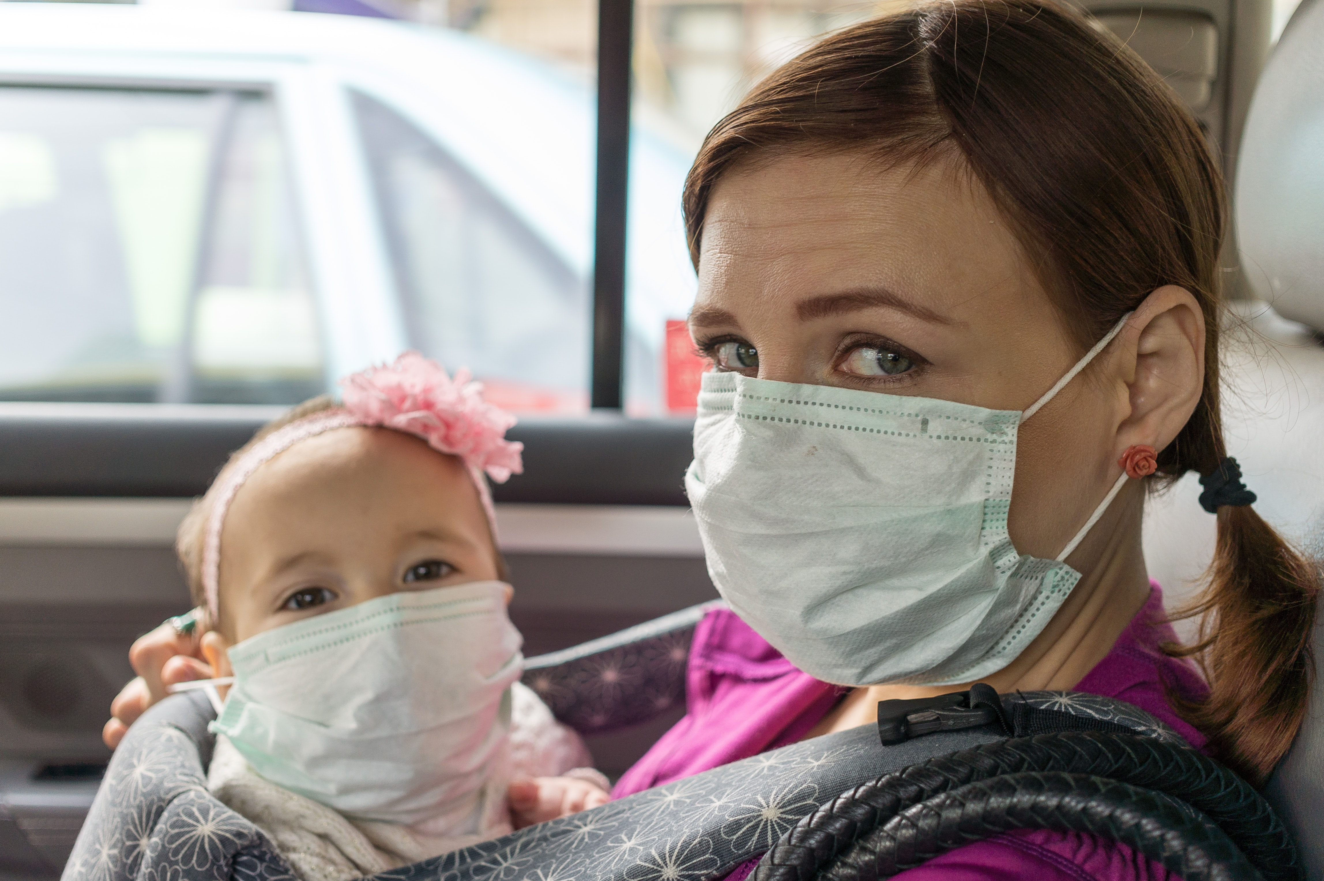 mom and baby wearing a medical mask