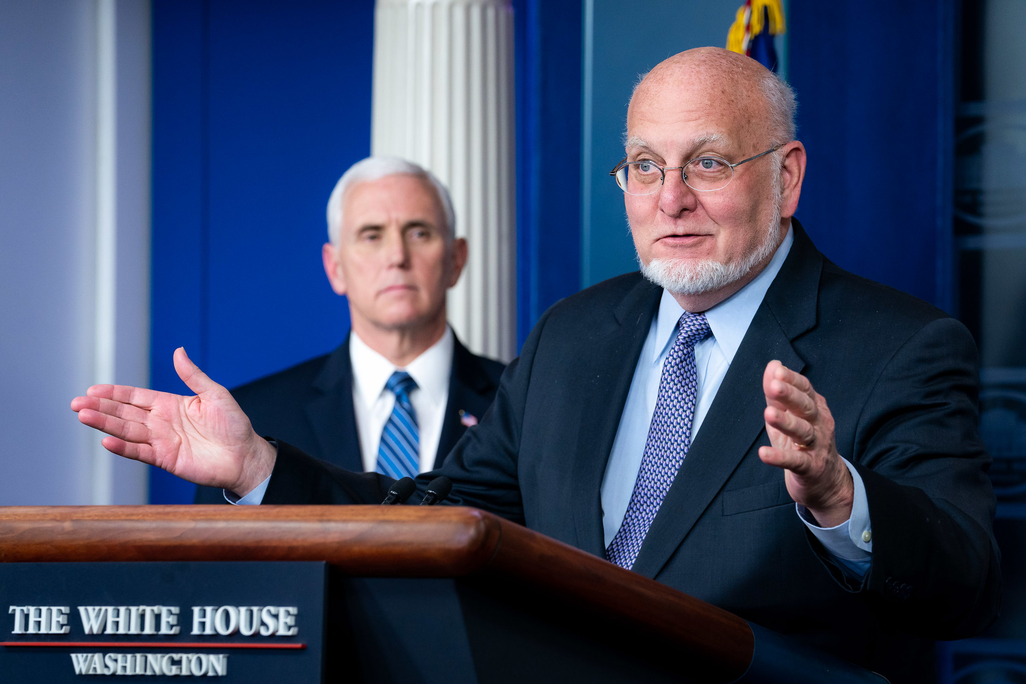 CDC Director Redfield speaks at a White House podium as Pence looks at him.