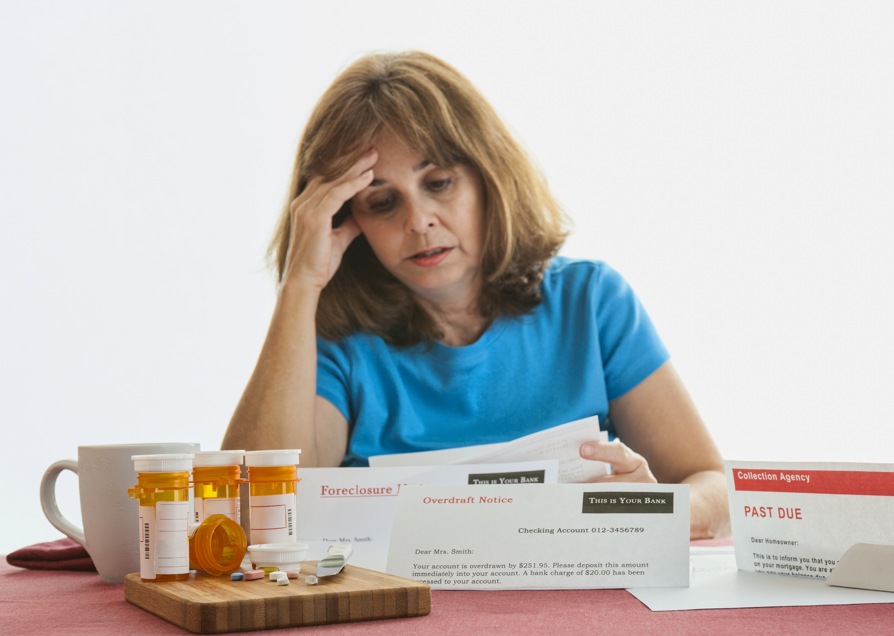 Woman looking at bills with prescription drugs on the table.