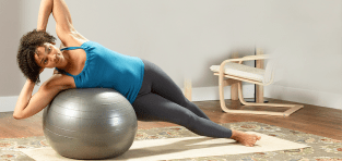 Woman working out on a mat with an exercise ball