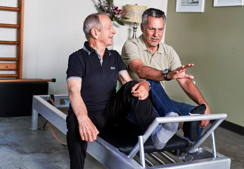 Photo of Jay Grimes and Ken Endelman seated together on a Reformer
