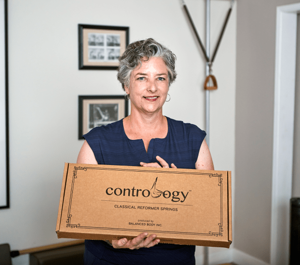 Photo of Karen Frischmann holding a Contrology Springs box