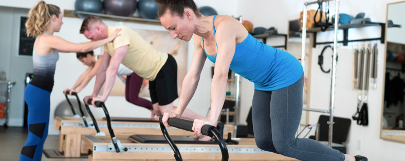 Master Instructors exercising on Pilates Reformers