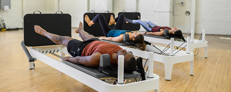 Photo of people working out on Allegro 2 Reformers using padded jumpboards